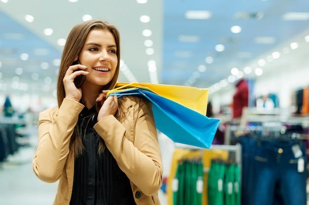 Młoda Kobieta Trzyma Torby Na Zakupy I Rozmawia Przez Telefon Darmowe Zdjęcia