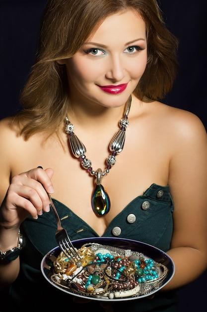 Młoda Kobieta Trzyma Widelec I Talerz Z Biżuterią Premium Zdjęcia