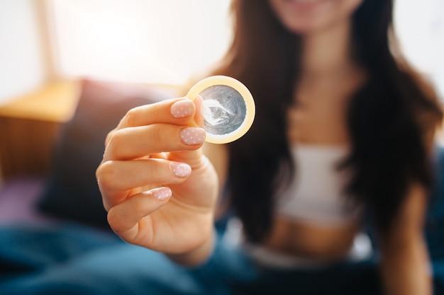 Młoda Kobieta Trzymać W Ręku Prezerwatywę. Bezpieczeństwo Seksualne Premium Zdjęcia