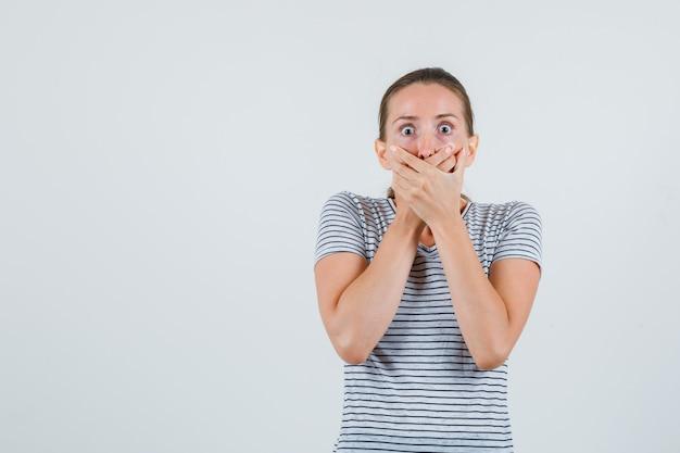 Młoda Kobieta Trzymając Się Za Ręce Na Ustach W T-shirt W Paski I Patrząc Przestraszony. Przedni Widok. Darmowe Zdjęcia