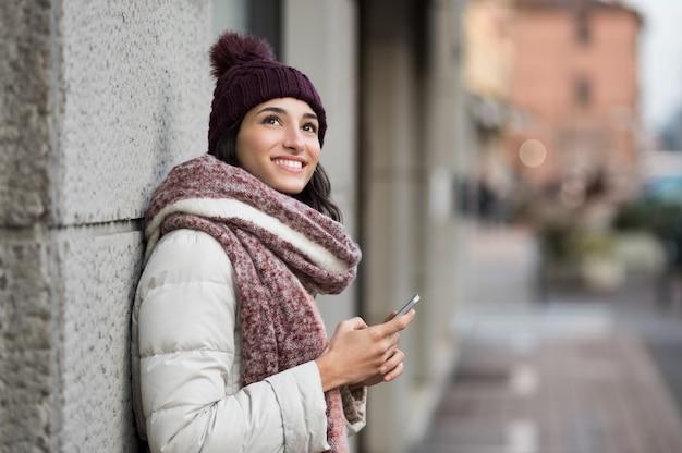 Młoda Kobieta Trzymając Smartfon I Patrząc W Górę Premium Zdjęcia
