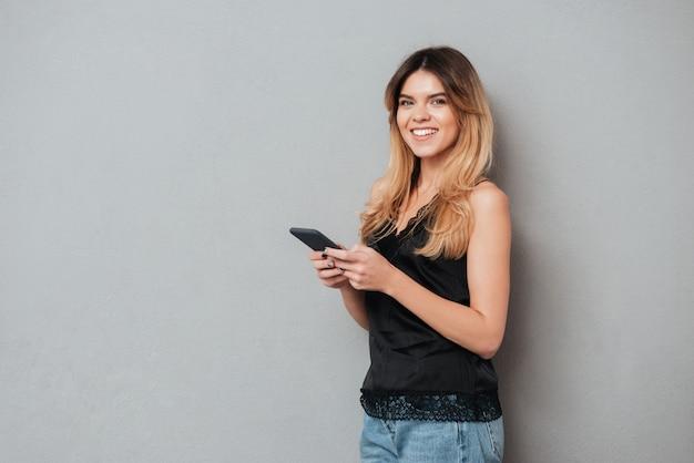 Młoda Kobieta Trzymając Telefon Komórkowy I Patrząc Na Kamery Darmowe Zdjęcia