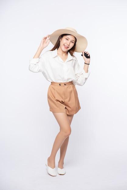 Młoda Kobieta Ubrana W Białą Koszulę I Szorty, Ubrana W Kapelusz I Uchwyt Na Kapeluszu Darmowe Zdjęcia