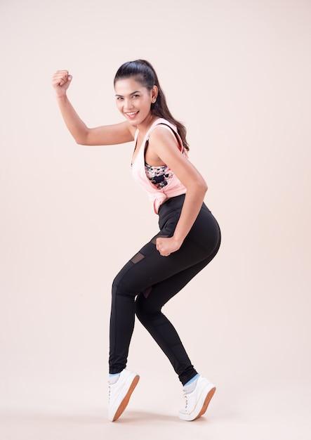 Młoda Kobieta Ubrana W Kombinezon Do ćwiczeń, Robi Taniec, Do ćwiczeń Premium Zdjęcia
