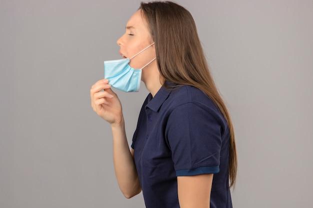 Młoda Kobieta Ubrana W Niebieską Koszulkę Polo Podnosząca Maskę Medyczną Usta Na Kaszel, Mdłości, Stojąc Na Jasnoszarym Na Białym Tle Darmowe Zdjęcia