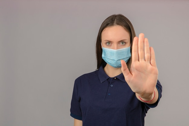 Młoda Kobieta Ubrana W Niebieską Koszulkę Polo W Ochronnej Masce Medycznej Pokazujący Gest Zatrzymania Ręki Z Poważną Twarzą Na Białym Tle Na Jasnoszarym Tle Z Miejsca Na Kopię Darmowe Zdjęcia