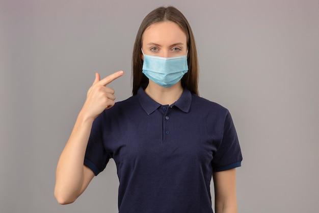 Młoda Kobieta Ubrana W Niebieską Koszulkę Polo W Ochronnej Masce Medycznej, Wskazując Palcem Na Jej Masce Z Poważną Twarzą Patrząc Na Kamerę Stojącą Na Jasnoszarym Tle Darmowe Zdjęcia