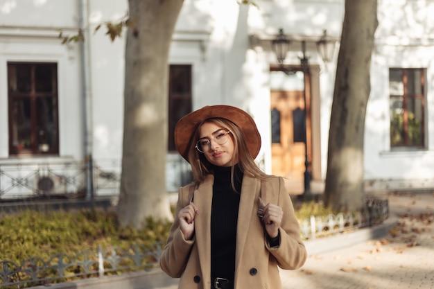Młoda Kobieta Ubrana W Płaszcz, Kapelusz I Plecak Spaceruje Po Jesiennym Europejskim Mieście Premium Zdjęcia