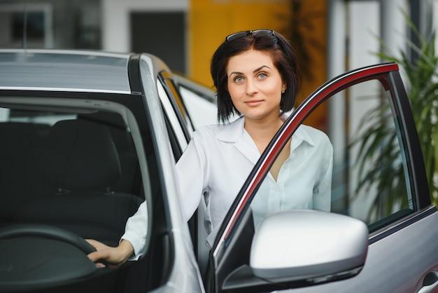 Młoda Kobieta Uśmiecha Się W Swoim Nowym Samochodzie W Salonie Premium Zdjęcia