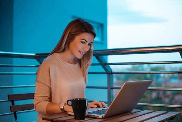 Młoda Kobieta Używa Laptop Na Domowym Balkonie. Premium Zdjęcia
