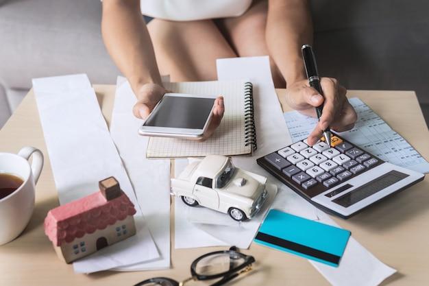Młoda kobieta używa mądrze telefon i sprawdza rachunki Premium Zdjęcia