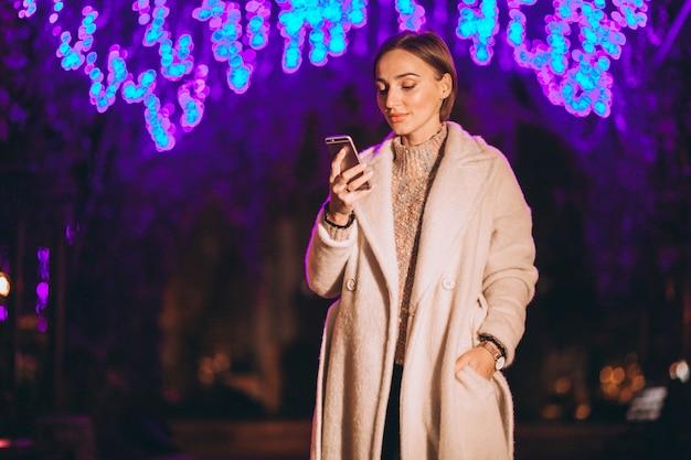 Młoda kobieta używa telefon na zewnątrz nocy ulicy Darmowe Zdjęcia