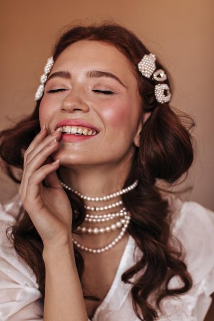 Młoda Kobieta W Białej Bluzce I Biżuterii Z Pereł śmieje Się. Migawka Kobiety Z Piegami Na Beżowym Tle. Darmowe Zdjęcia