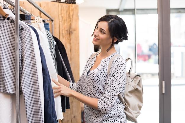 Młoda Kobieta W Butiku Wybierając Nowe Ubrania Do Kupienia Premium Zdjęcia