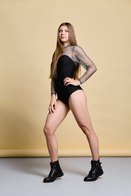 Młoda Kobieta W Ciasnym Body I Szorstkich Butach Pozowanie W Studio Na Bladożółtym Premium Zdjęcia