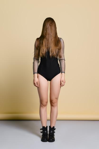 Młoda Kobieta W Ciasnym Kolorze Ciała I Szorstkich Butach Stojących Prosto Z Włosami Na Twarzy W Studio Premium Zdjęcia
