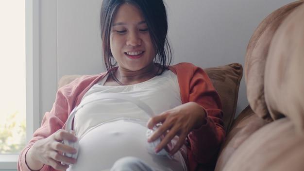 Młoda Kobieta W Ciąży Azji Przy Użyciu Telefonu I Słuchawek Odtwarzać Muzykę Dla Dziecka W Brzuchu. Mama Czuje Się Szczęśliwy Uśmiechnięty Pozytywny I Pokojowy Podczas Gdy Dbamy Dziecka Leżącego Na Kanapie W żywym Pokoju W Domu. Darmowe Zdjęcia