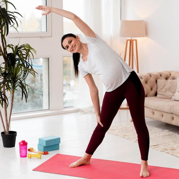 Młoda Kobieta W Ciąży ćwiczenia Na Macie Fitness Darmowe Zdjęcia