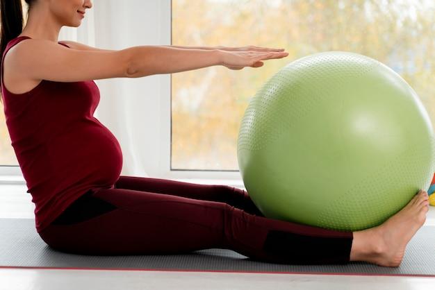 Młoda Kobieta W Ciąży ćwiczy Z Zieloną Piłkę Fitness Darmowe Zdjęcia