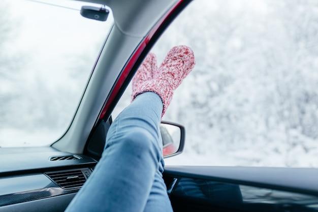 Młoda Kobieta W Ciepłych Skarpetkach Odpoczywa Wewnątrz Samochodu, Zbliżenie. Premium Zdjęcia