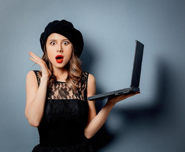 Młoda Kobieta W Czerni Sukni Z Notatnikiem Na Szarości ścianie Premium Zdjęcia