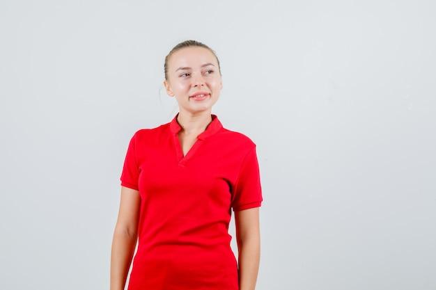 Młoda Kobieta W Czerwonej Koszulce, Patrząc Z Dala I Patrząc Optymistycznie Darmowe Zdjęcia