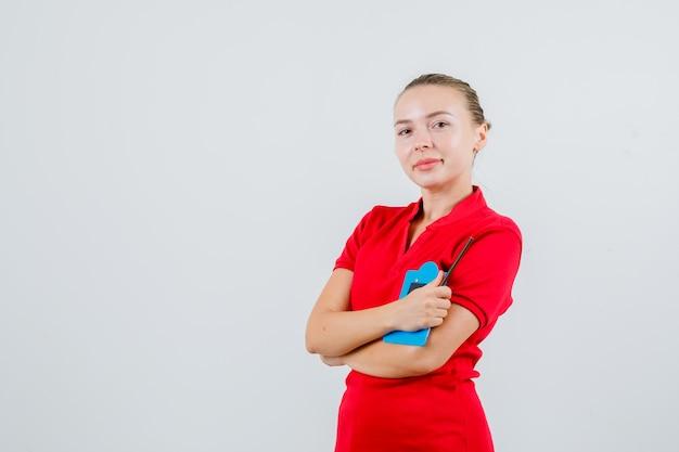Młoda Kobieta W Czerwonej Koszulce, Trzymając Mini Schowek I Patrząc Optymistycznie Darmowe Zdjęcia