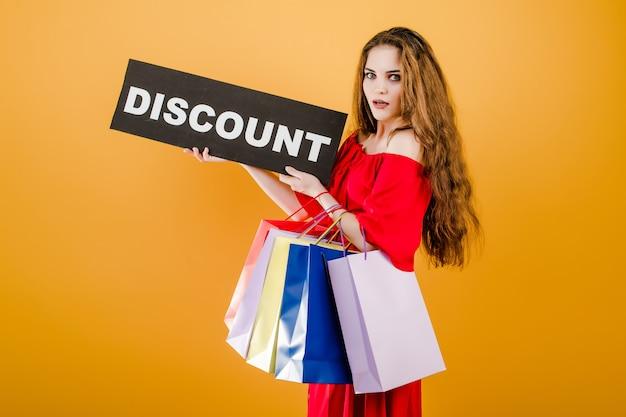 Młoda kobieta w czerwonej sukience ze znakiem zniżki i kolorowe torby na zakupy na białym tle nad żółtym Premium Zdjęcia
