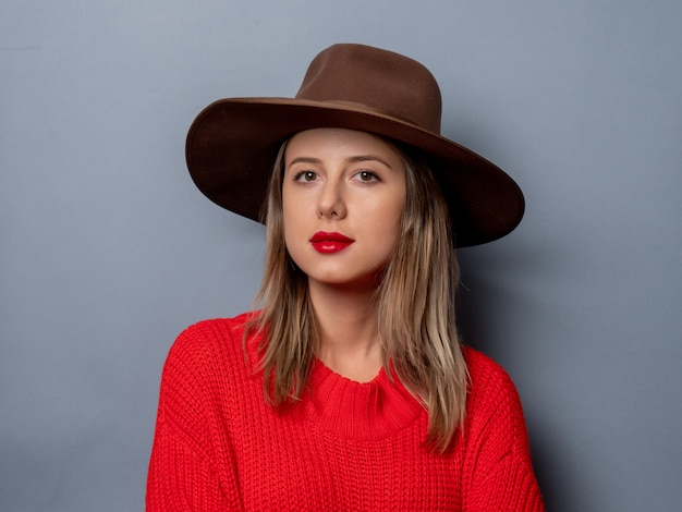 Młoda kobieta w czerwonym swetrze i kapeluszu Premium Zdjęcia
