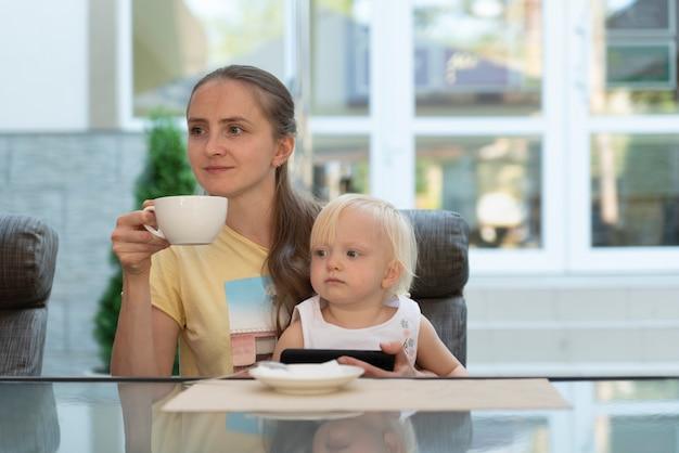 Młoda Kobieta W Kawiarni Z Dzieckiem W Ramionach Pije Kawę I Patrzy Na Telefon. Nowoczesna Mama Biznesowa. Premium Zdjęcia