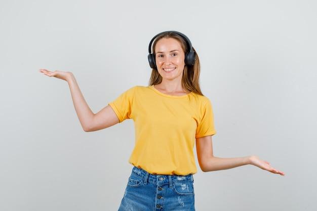 Młoda Kobieta W Koszulce, Spodenkach, Słuchawkach, Podnosząc Ręce, Aby Pokazać Równowagę I Zadowolony Darmowe Zdjęcia