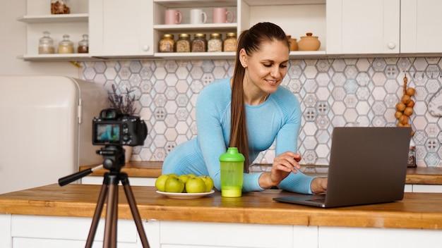 Młoda Kobieta W Kuchni Z Laptopem Uśmiecha Się. Koncepcja Blogera żywności. Kobieta Nagrywa Film O Zdrowym Odżywianiu. Aparat Na Statywie. Premium Zdjęcia