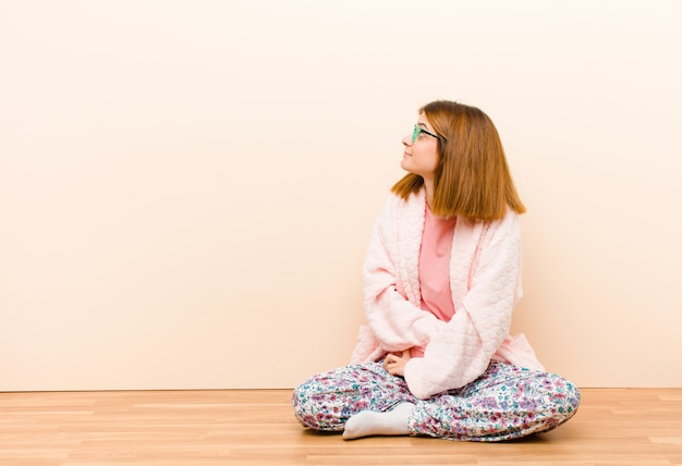 Młoda kobieta w piżamie siedzi w domu czując się zagubiona lub pełna lub wątpliwości i pytania, zastanawiając się, z rękami na biodrach, widok z tyłu Premium Zdjęcia