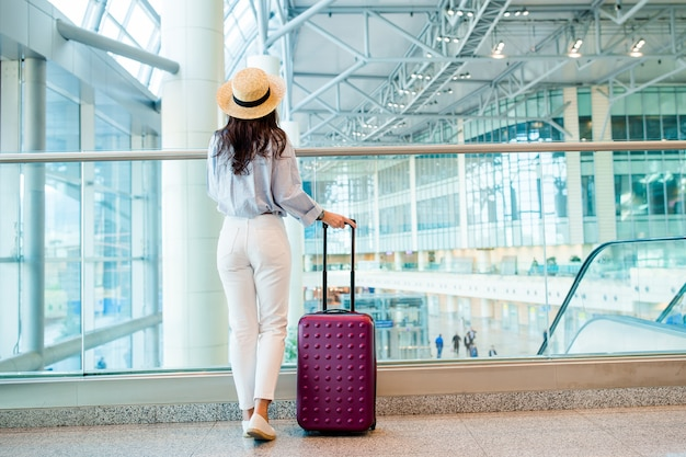 Młoda kobieta w poczekalni na lotnisku w poczekalni. Premium Zdjęcia