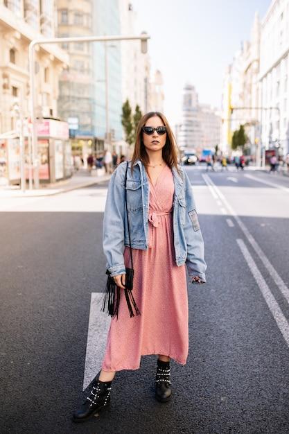 Młoda kobieta w różowej sukience, dżinsowej kurtce, butach i okularach przeciwsłonecznych kota stojących przy słynnym widoku gran via głównej drogi broadway w centrum madrytu, hiszpania. Premium Zdjęcia