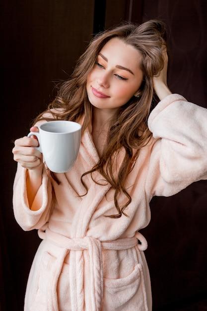 Młoda Kobieta W Różowy Szlafrok Przetargu Pić Herbatę I Uśmiechając Się. Darmowe Zdjęcia