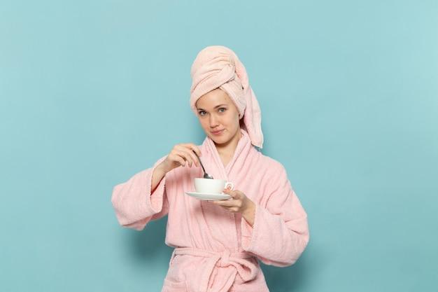 Młoda Kobieta W Różowym Szlafroku Po Prysznic Mieszanie Kawy Na Niebiesko Darmowe Zdjęcia