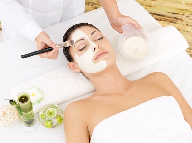 Młoda Kobieta W Salonie Spa Z Kosmetyczną Maską Na Twarzy. Zdjęcie Pod Dużym Kątem Darmowe Zdjęcia