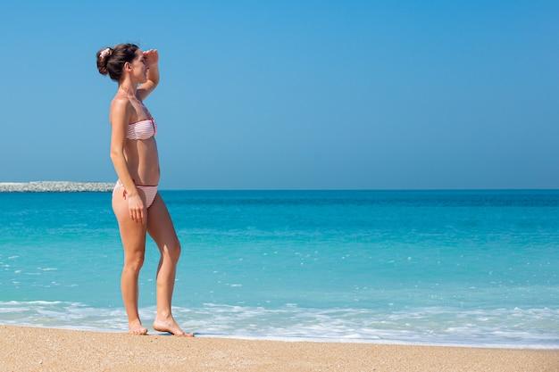 Młoda Kobieta W Stroju Kąpielowym Patrzy W Dal Na Ocean Premium Zdjęcia
