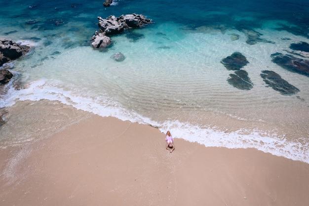 Młoda Kobieta W Sukni Leżącej Na Plecach Na Białym Piasku W Pobliżu Fal Błękitnego Morza. Widok Z Góry, Morze Andamańskie, Phuket, Tajlandia. Antenowy Premium Zdjęcia