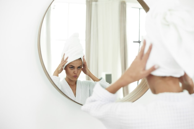 Młoda Kobieta W Szlafroku Patrząc W Lustro W łazience. Czyste Piękno. Atrakcyjna Kobieta Dotyka Jej Twarzy I Uśmiecha Się, Patrząc W Lustro. Premium Zdjęcia