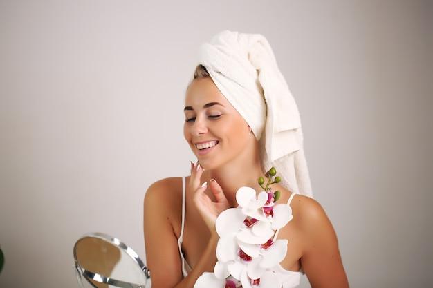 Młoda Kobieta W Szlafroku Z Orchideą Premium Zdjęcia