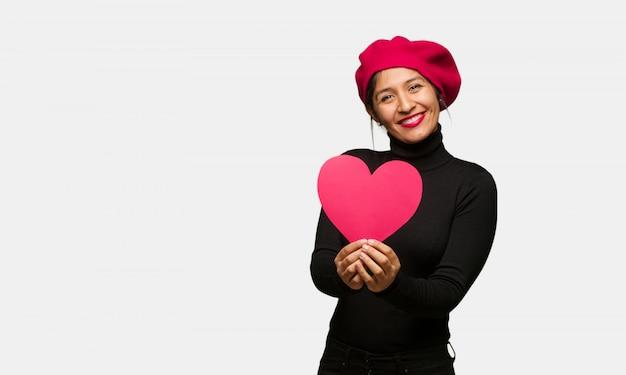 Młoda kobieta w valentines dniu robi kierowemu kształtowi z rękami Premium Zdjęcia
