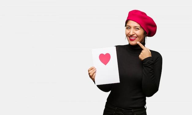 Młoda kobieta w valentines dzień uśmiechach, wskazujący usta Premium Zdjęcia
