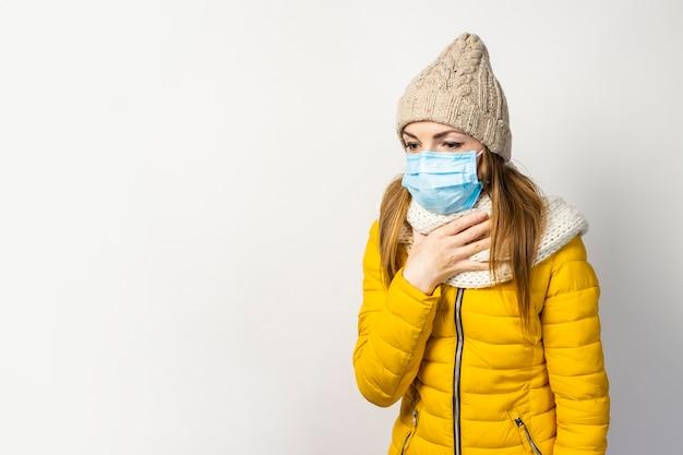 Młoda Kobieta W żółtej Kurtce I Kapeluszu Z Maską Medyczną Na Białym Tle Premium Zdjęcia