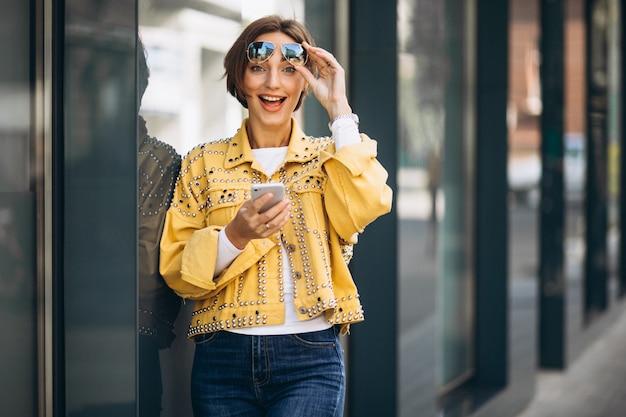 Młoda kobieta w żółtej kurtce używać telefon outside w ulicie Darmowe Zdjęcia