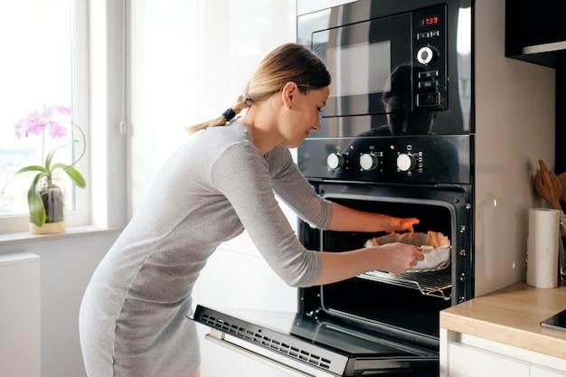 Młoda Kobieta Wkłada Domowe Ciasto Do Piekarnika Darmowe Zdjęcia