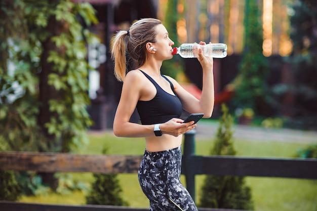 Młoda Kobieta Wody Pitnej Po Uruchomieniu I Korzystaniu Z Inteligentnego Telefonu Na Zielonej ścianie Parku. Premium Zdjęcia
