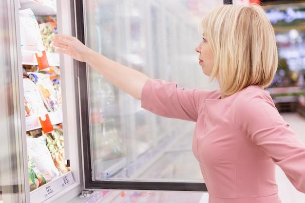 Młoda Kobieta Wybiera Mrożone Jedzenie W Supermarkecie. Premium Zdjęcia