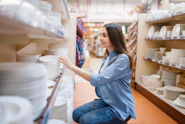Młoda Kobieta Wybiera Talerze W Sklepie Agd. Kobieta Kupuje Artykuły Domowe Na Rynku, Pani W Sklepie Z Artykułami Kuchennymi Premium Zdjęcia